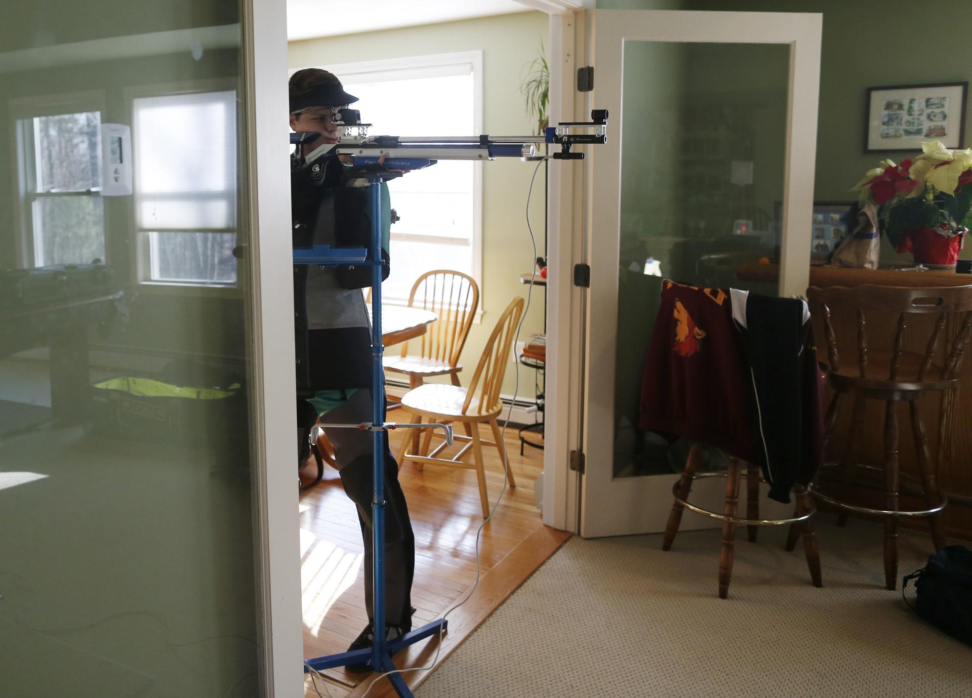 Tyler Lefebvre, 17, a member of the Taunton Marksmanship Unit, practiced shooting with an air rifle in the living room of his home in Uxbridge, Mass.